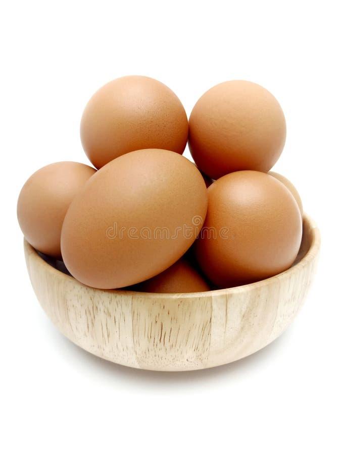 Oeufs bruns frais crus de poulet dans la cuvette en bois photos stock