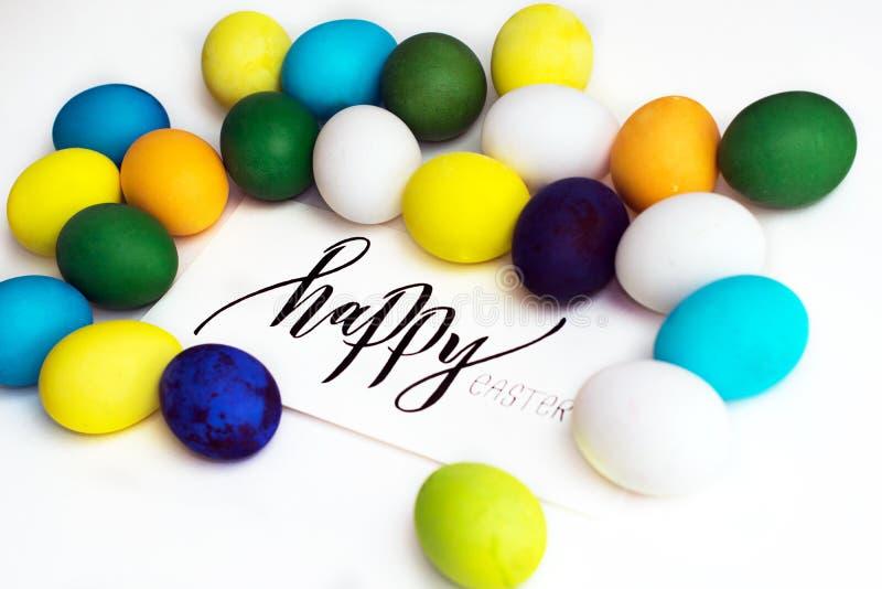 Oeufs colorés de fête de Pâques sur un fond blanc avec un ` heureux de Pâques de ` de calligraphie de carte de voeux oeufs jaune, image stock