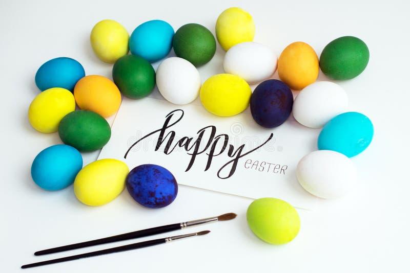 Oeufs colorés de fête de Pâques sur un fond blanc avec un ` heureux de Pâques de ` de calligraphie de carte de voeux oeufs jaune, image libre de droits