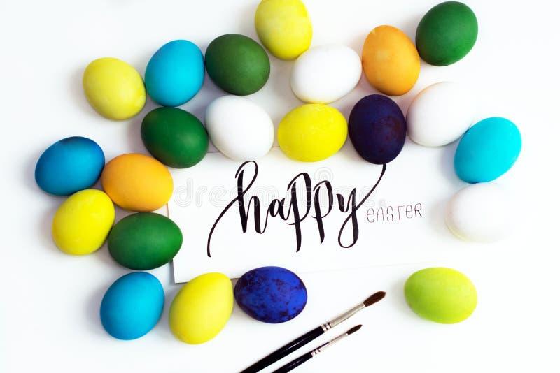 Oeufs colorés de fête de Pâques sur un fond blanc avec un ` heureux de Pâques de ` de calligraphie de carte de voeux oeufs jaune, photographie stock