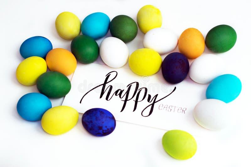 Oeufs colorés de fête de Pâques sur un fond blanc avec un ` heureux de Pâques de ` de calligraphie de carte de voeux oeufs jaune, photo libre de droits