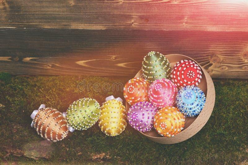 Oeufs colorés de Pâques sur la mousse verte décorée du fil, perles photographie stock libre de droits