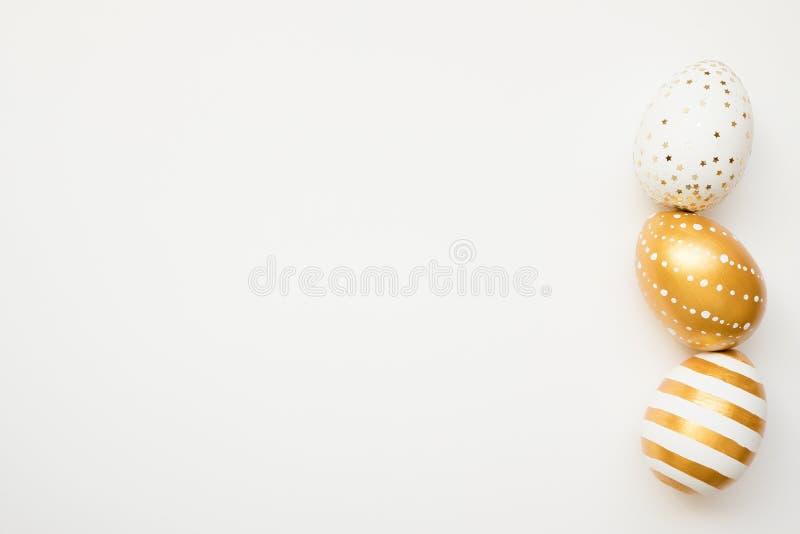 Oeufs décorés d'or de Pâques d'isolement sur le fond blanc Concept minimal de Pâques Carte de Pâques heureuse avec l'espace de co photo libre de droits