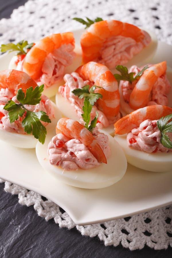 Oeufs délicieux bourrés de la fin de fruits de mer sur la table Verti photos stock