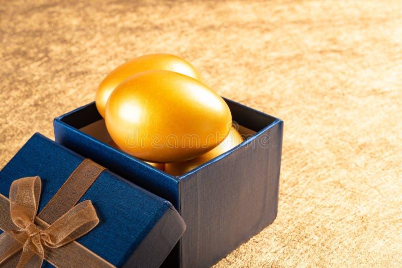 Oeufs d'or dans la boîte actuelle sur le fond d'or photo stock