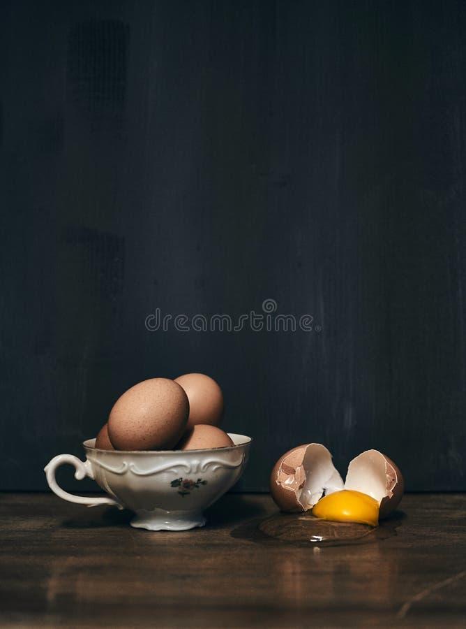 Oeufs dans la tasse de porcelaine avec l'oeuf criqué à coté sur la table de cru images stock