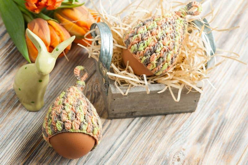 Oeufs dans les chapeaux tricotés, les tulipes et le lapin décoratif images stock