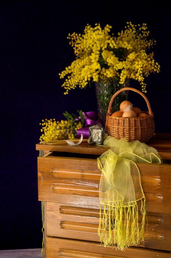 Oeufs dans un panier en osier, un bouquet de mimosa et des bougies d'église photos libres de droits