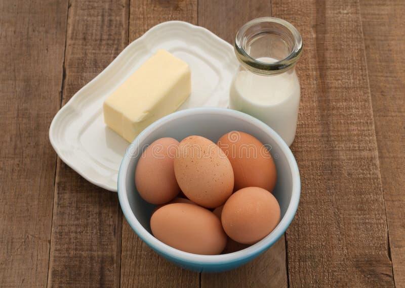 Oeufs de Brown, lait, et beurre dans la configuration de pays photographie stock libre de droits