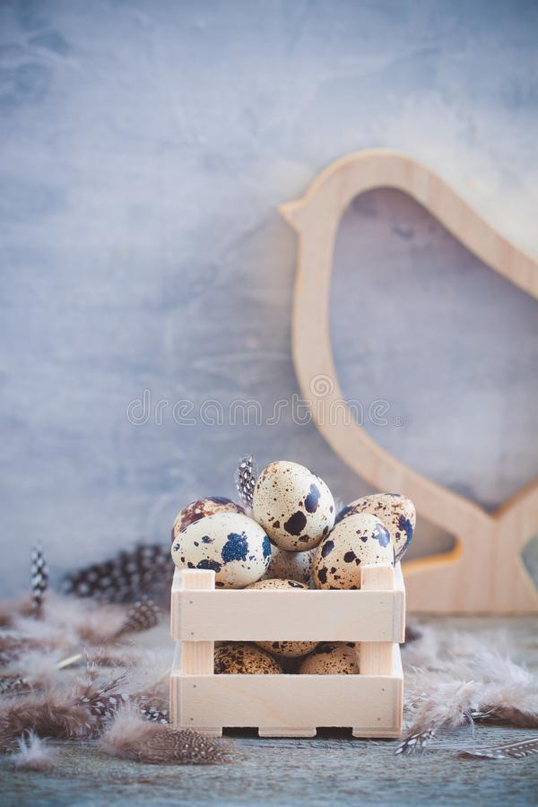 Oeufs de caille dans la boîte en bois avec des plumes sur le fond rustique Concept de carte postale de ressort de Pâques photo stock