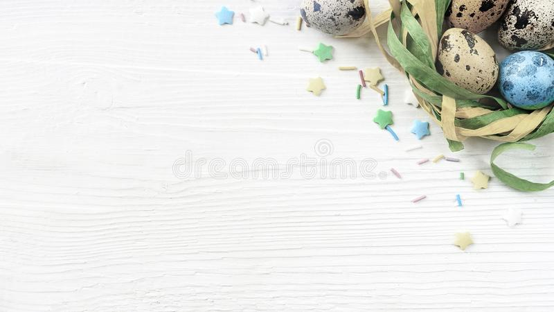Oeufs de caille de Pâques avec des décorations sur le fond en bois blanc photographie stock