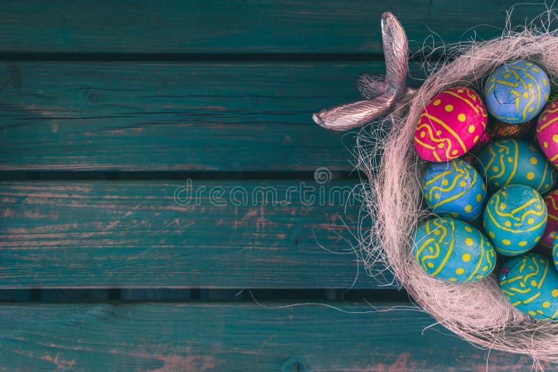 Oeufs de choclate de Pâques, cuvette d'ester, banc vert, fond de Pâques image stock