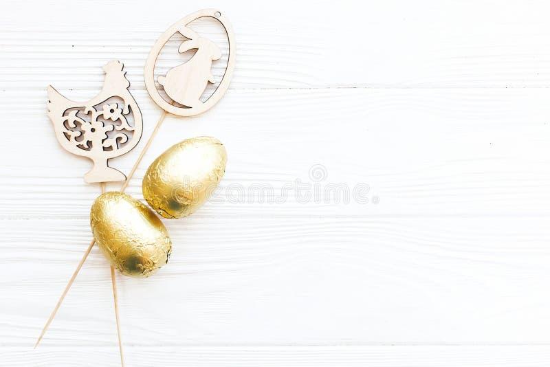 Oeufs de chocolat élégants de Pâques dans l'aluminium d'or et décorations en bois simples de lapin et de poulet sur le fond en bo images stock