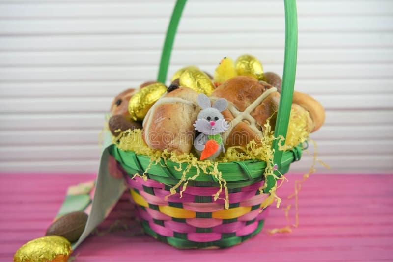 Oeufs de chocolat d'or d'aluminium avec la décoration mignonne de lapin de Pâques et les petits pains croisés chauds image libre de droits