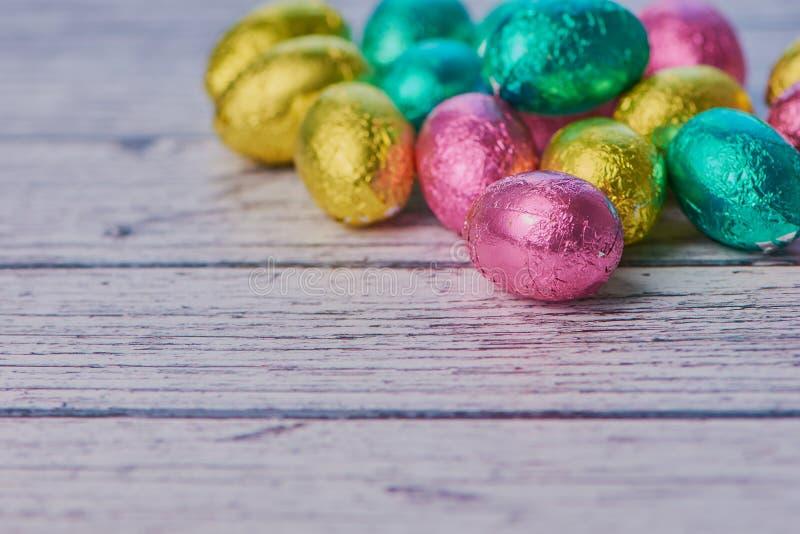 Oeufs de chocolat enveloppés colorés sur le fond en bois blanc photo stock