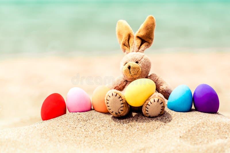 Oeufs de lapin et de couleur de Pâques sur la plage sablonneuse par photos libres de droits