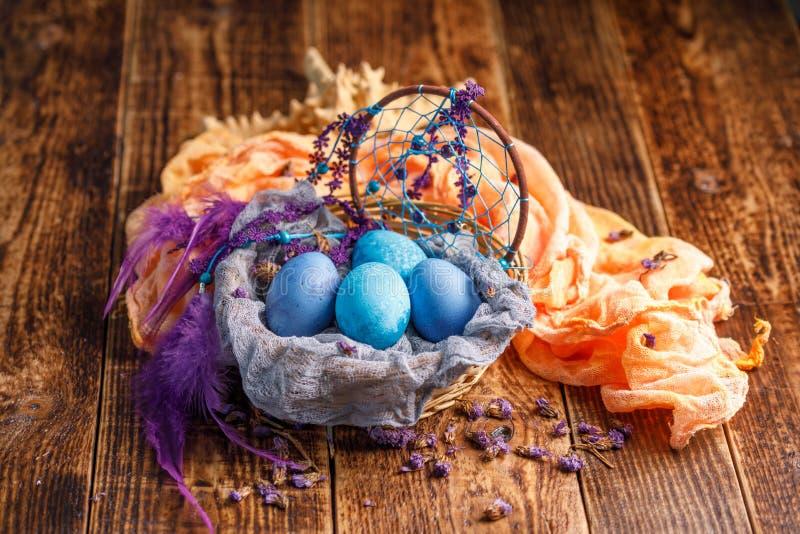 Oeufs de pâques à l'origine peints dans un panier en osier avec un bel attribut du receveur rêveur image stock