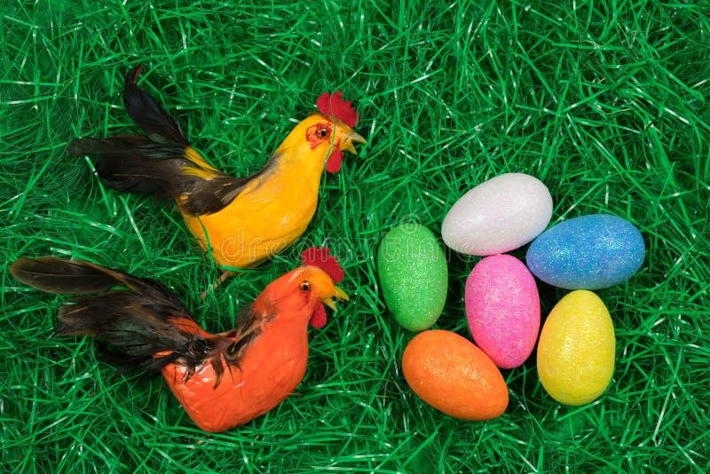 Oeufs de pâques éclatants colorés dans l'herbe artificielle verte et deux figures de poulet photographie stock