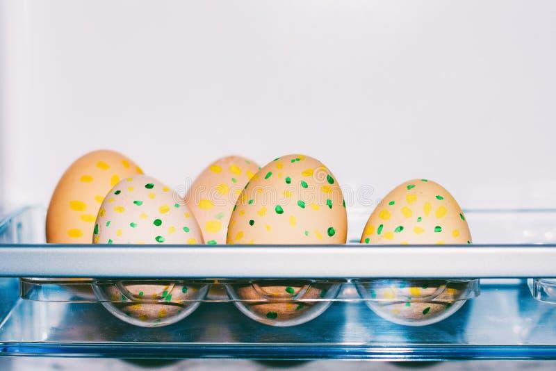 Oeufs de pâques avec le modèle des points jaunes et verts dans le plateau en plastique dans le réfrigérateur avec l'espace de cop photographie stock