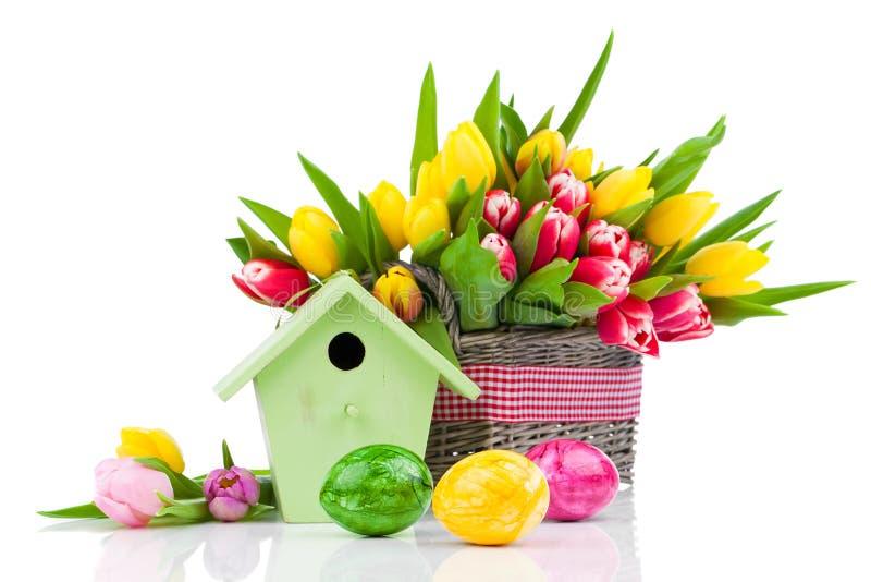 Oeufs de pâques avec les fleurs et la volière de tulipes, images libres de droits