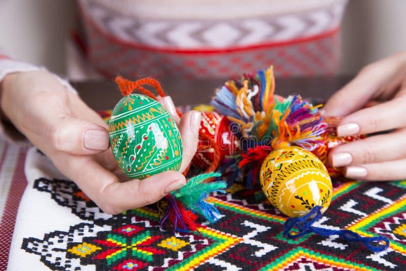 Oeufs de pâques colorés avec des conceptions traditionnelles dans des mains femelles photos stock