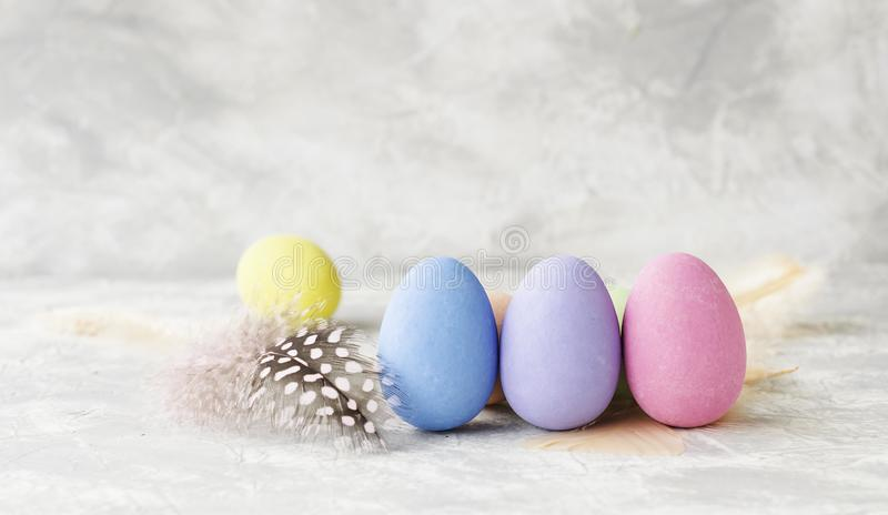 Oeufs de pâques colorés avec des plumes sur une table blanche de marbre, foyer sélectif image stock