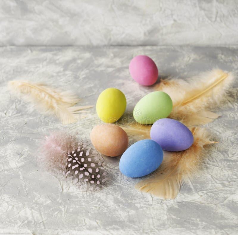 Oeufs de pâques colorés avec des plumes sur une table blanche de marbre, foyer sélectif photo stock