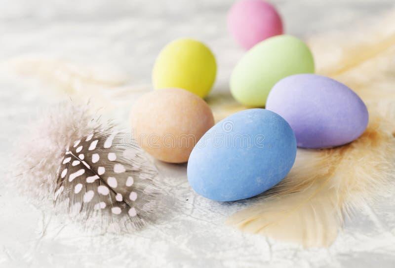 Oeufs de pâques colorés avec des plumes sur une table blanche de marbre, foyer sélectif photographie stock libre de droits