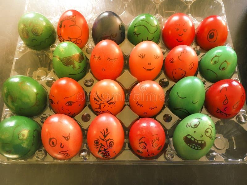 Oeufs de pâques colorés décorés des visages drôles photo libre de droits