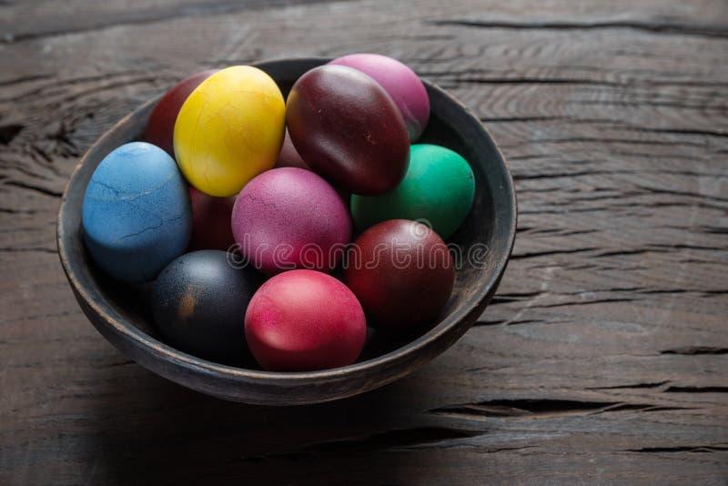 Oeufs de pâques colorés dans la cuvette sur la table en bois Attribut de célébration de Pâques photo libre de droits