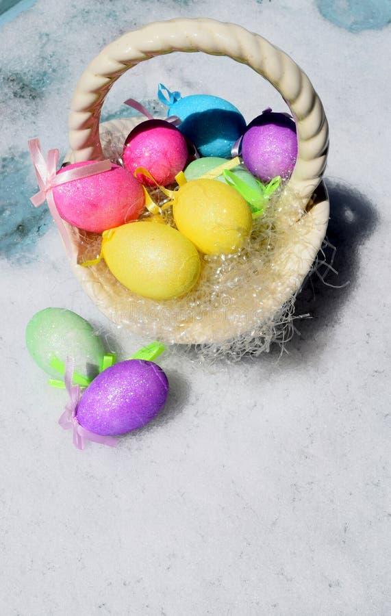Oeufs de pâques colorés dans la neige image stock