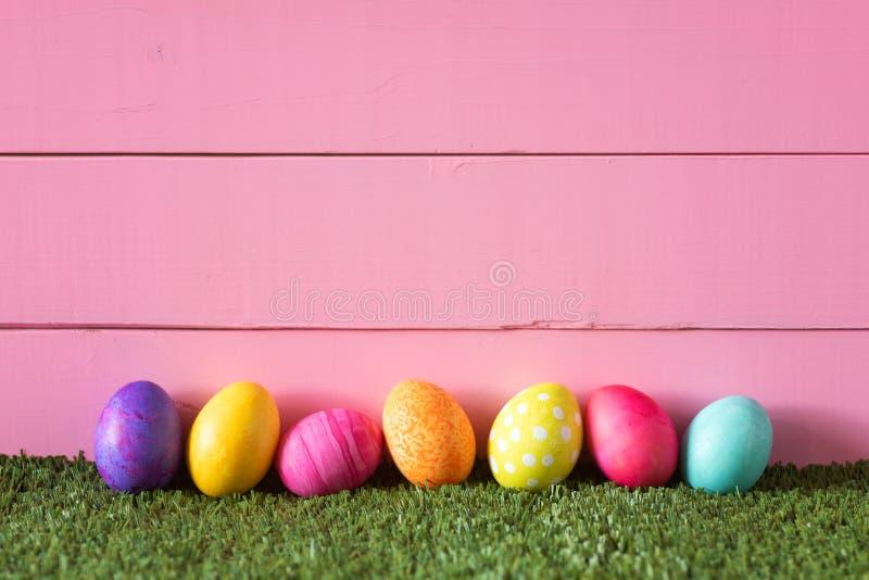 Oeufs de pâques colorés dans la rangée sur le fond du fond en bois rose de mur de conseils et pose dans l'herbe verte avec la piè photographie stock libre de droits