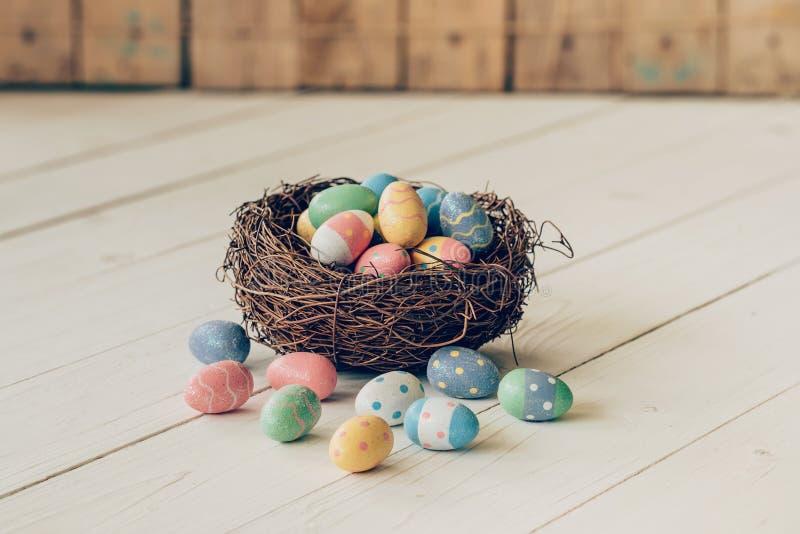 Oeufs de pâques colorés dans le nid sur le fond en bois de table photos stock
