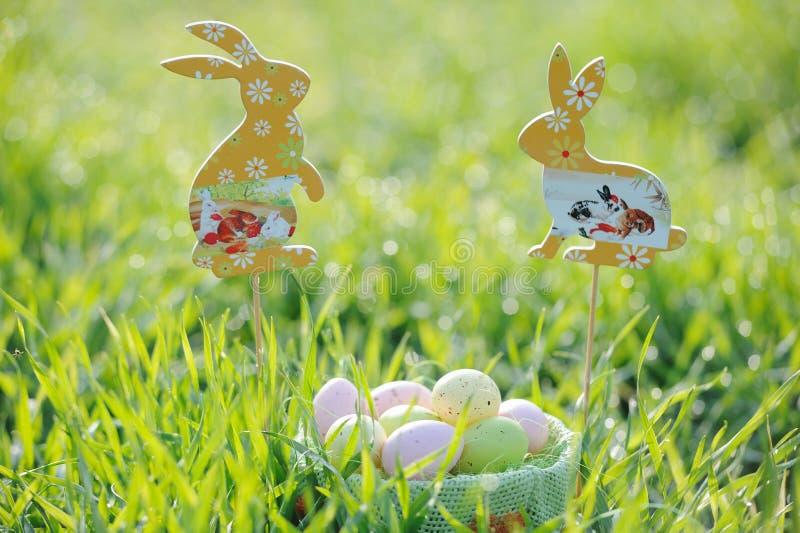 Oeufs de pâques colorés dans un panier avec des décorations de lapin photographie stock