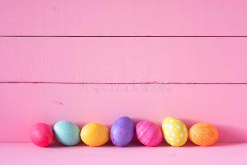 Oeufs de pâques colorés dans une rangée sur un Tableau et sur un fond rose lumineux de mur de conseil avec l'espace de copie Hori photo libre de droits
