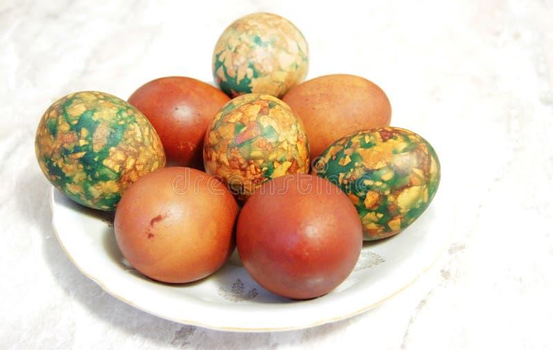 Oeufs de pâques colorés du plat blanc placé par le tas photos libres de droits
