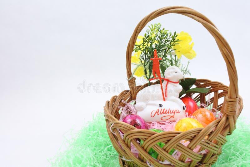 Oeufs de pâques colorés et agneau blanc dans un panier en osier images libres de droits