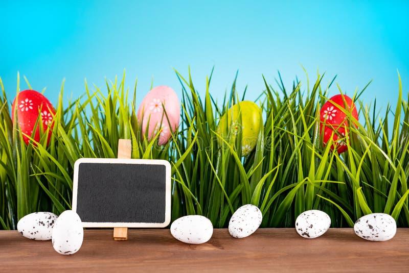Oeufs de pâques colorés et herbe verte avec le fond de salutation de table en bois images libres de droits
