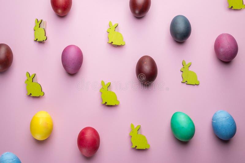 Oeufs de pâques colorés et lapins de Pâques en bois comme attribut de célébration de Pâques Fond rose photographie stock libre de droits