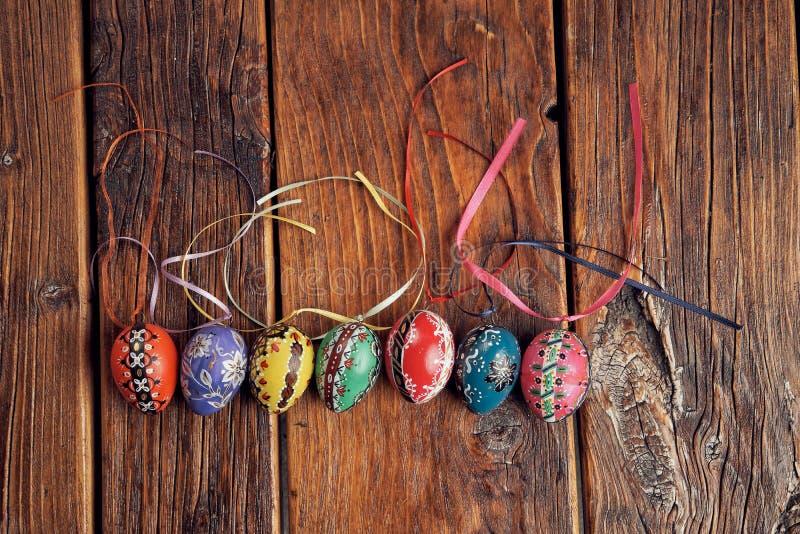 Oeufs de pâques colorés, peint à la main, disposés dans une ligne avec l'espace sur le dessus sur une table en bois de cru photo libre de droits