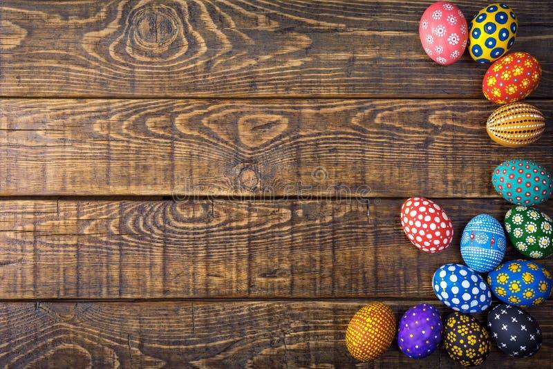 Oeufs de pâques colorés peints à la main sur le fond en bois rustique avec l'espace photo stock