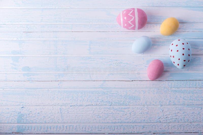 Oeufs de pâques colorés peints à la main sur un fond bleu Carte de ressort de vacances images stock
