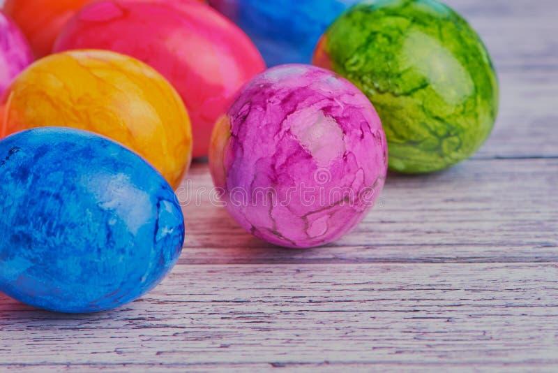 Oeufs de pâques colorés sur la surface en bois blanche avec l'espace de copie image libre de droits