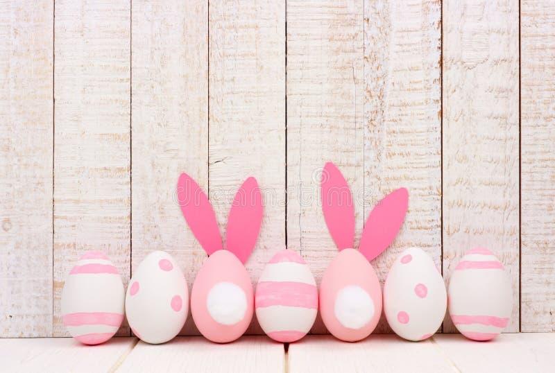 Oeufs de pâques contre le bois blanc, deux avec des queues de lapin et oreilles image libre de droits
