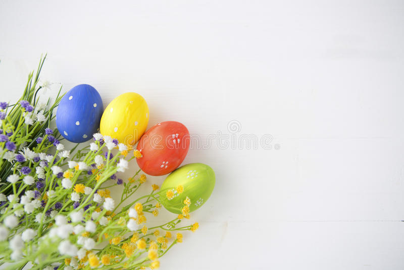 Oeufs de pâques décorés colorés sur le fond en bois blanc images stock