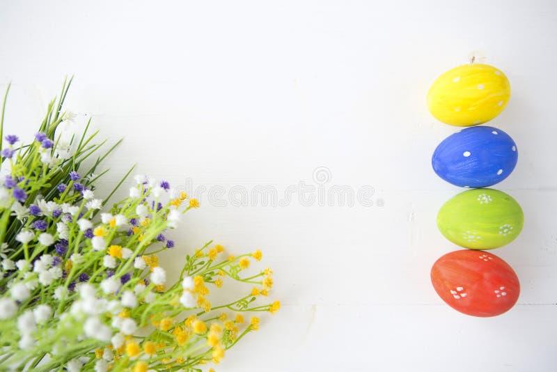 Oeufs de pâques décorés colorés sur le fond en bois blanc photo stock
