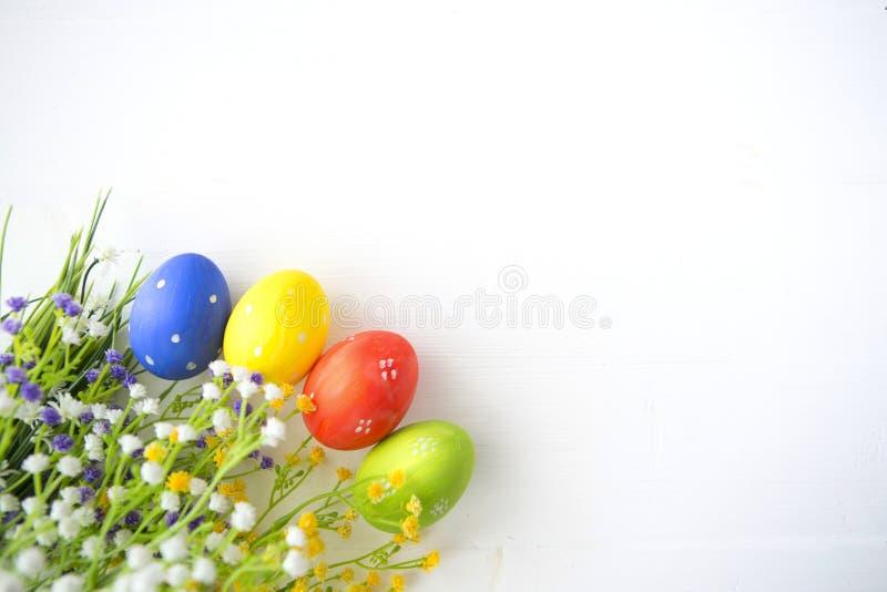 Oeufs de pâques décorés colorés sur le fond en bois blanc image stock