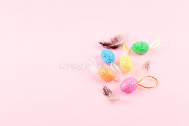 Oeufs de pâques décoratifs avec des plumes sur le fond rose Composition en Pâques, carte de voeux avec les oeufs décoratifs multi image libre de droits