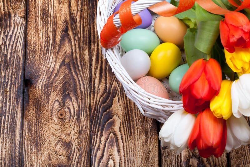 Oeufs de pâques dans un panier blanc avec les tulipes colorées images libres de droits