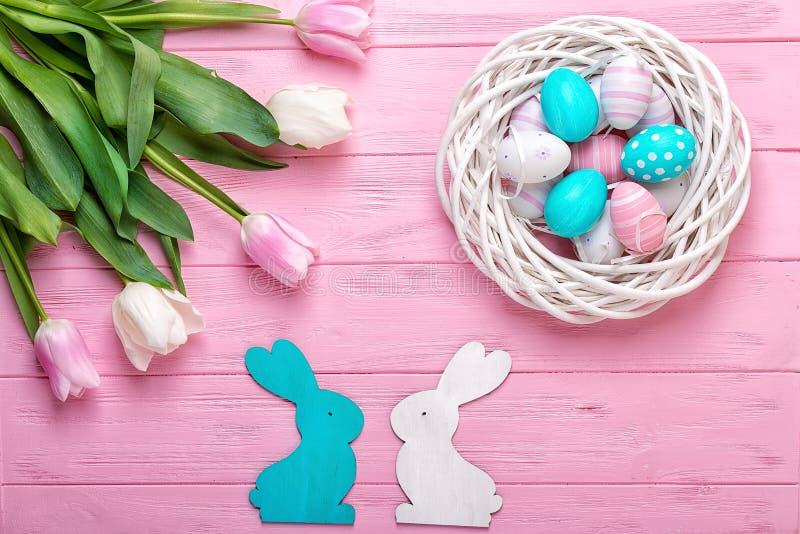 Oeufs de pâques dans un panier en osier et tulipes de bouquet sur le fond en bois Concept de vacances de Pâques images stock